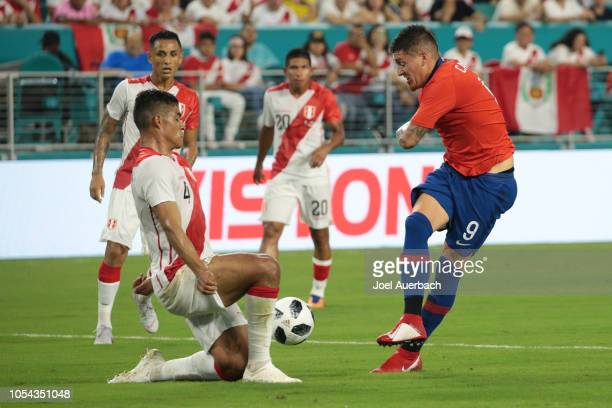 Anderson Santamaría of Peru blocks the shot by Nicolas Castillo of Chile during an International friendly match on October 12 2018 at Hard Rock...