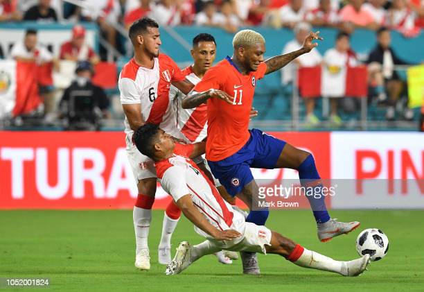 Anderson Santamaría of Peru slide tackles Junior Fernanades of Chile during the International Friendly 'Clasico del Pacifico at Hard Rock Stadium on...