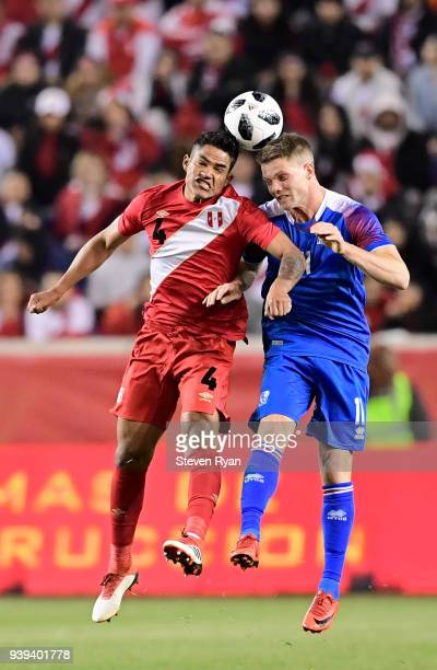 Anderson Santamaria of Peru and Björn Sigurðarson of Iceland battle for a header in an International Friendly match at Red Bull Arena on March 27...