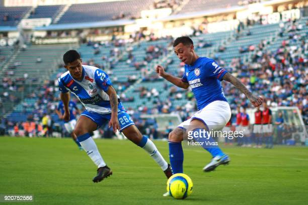 Anderson Santamaria of Puebla struggles for the ball with Martin Rodriguez of Cruz Azul during the 8th round match between Cruz Azul and Puebla as...