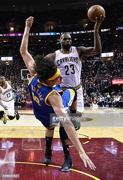 Anderson Varejao of the Golden State Warriors falls as LeBron James of the Cleveland Cavaliers drives to the basket during the second half in Game 3...