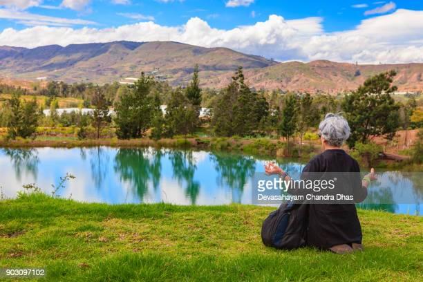 anden - senior kolumbianische lady meditiert in der ruhigen umgebung von der pozos azules in der nähe der stadt von villa de leyva in der kolumbien-abteilung von boyacá - kieferngewächse stock-fotos und bilder