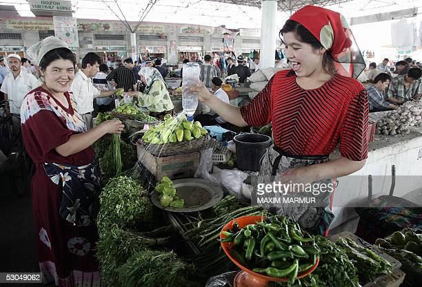 An Uzbek woman sprays water on greens at the central market in the eastern city of Andijan Uzbekistan 10 June 2005 Fifty people detained in...