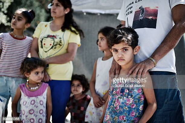 Ando Elias Tareq a Yezidi from Sinjar in Iraq stands behind his daughter outside the Samos hotspot where they live on September 1 2016 Tareq still...