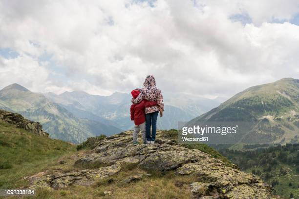 andorra, ordino, young girl and her brother, arm around, standing on viewpoint in the mountain - andorra stock pictures, royalty-free photos & images