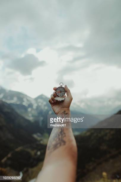 andorra, tattooed man holding compass, partial view - compass stock pictures, royalty-free photos & images