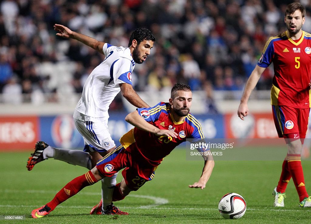Andorra's Jordi Rubio falls in front of Cypriot player Nestor Mytidis during their Euro 2016 Group B qualifying match at the GSP Stadium in the capital Nicosia on November 16, 2014.