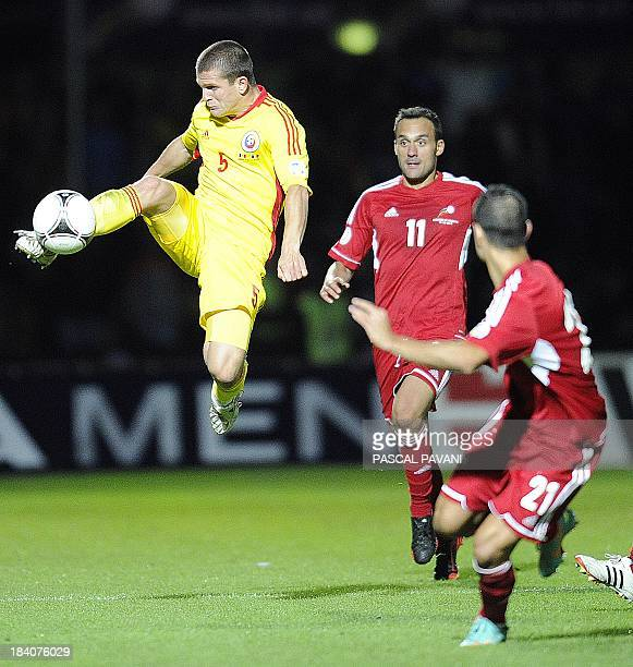 Andorra's midfielder Sergi Moreno vies with Romanian's defender Alexandru Bourceanu during the World Cup 2014 qualifying football match group D...