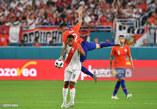 André Carrillo of Peru defends against Eugenio Mena of Chile during the International Friendly 'Clasico del Pacificoat Hard Rock Stadium on October...