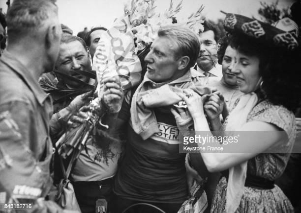 André Darrigade vainqueur de la 1ère étape ReimsLiège du Tour de France 1956 endosse le maillot jaune aidé par Yvette Horner à Liège Belgique le 5...