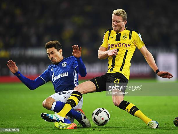 André Schürrle of Dortmund is challenged by Benjamin Stambouli of Schalke during the Bundesliga match between Borussia Dortmund and FC Schalke 04 at...