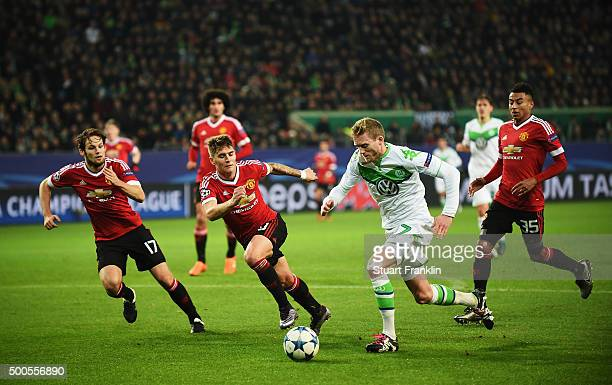 André Schürrle of Wolfsburg is challenged by Guillermo Varela of Manchester during the UEFA Champions League match between VfL Wolfsburg and...