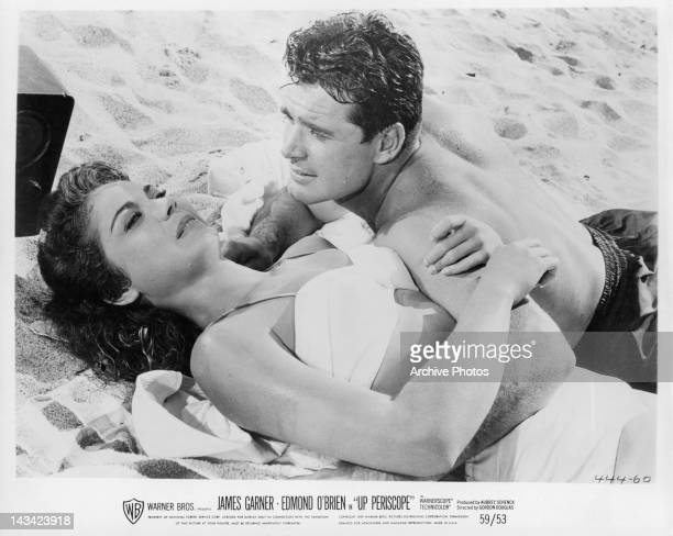 Andra Martin and James Garner laying on the beach together in a scene from the film 'Up Periscope' 1959
