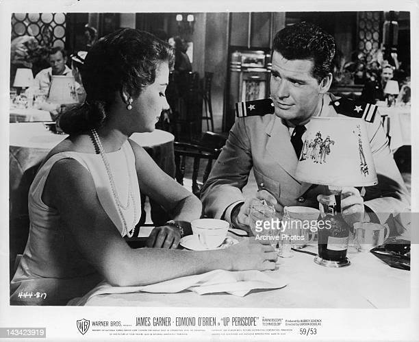Andra Martin and James Garner sitting at table together in a scene from the film 'Up Periscope' 1959