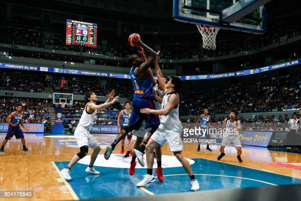 Andray Blatche of team Philippines powers his way to basket against three team Japan players during the qualifying game at the MOA Arena The...