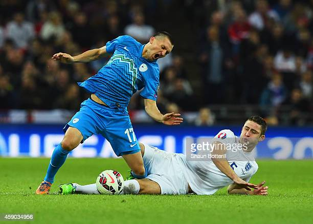 Andraz Kirm of Slovenia is challenged by Gary Cahill of England during the EURO 2016 Qualifier Group E match between England and Slovenia at Wembley...