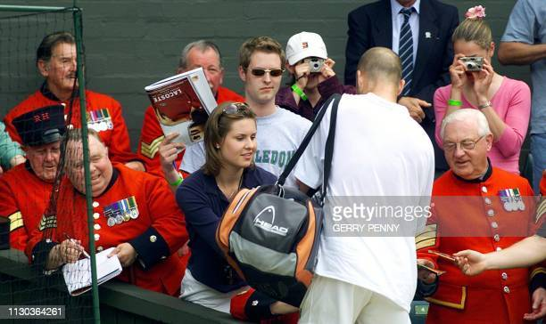 US Andre Agassi gives autographs to Chelsea Pensioners war veterans after his second round match against Britain's Jamie Delgado at the All England...
