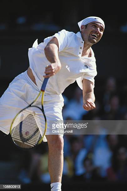 Andre Agassi of the UInited States serves to Boris Becker during their Men's Singles semi final match at the Wimbledon Lawn Tennis Championships on...