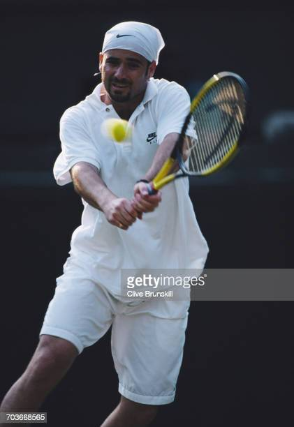Andre Agassi of the United States makes a double backhand return against Todd Martin during their Fourth Round match at the Wimbledon Lawn Tennis...