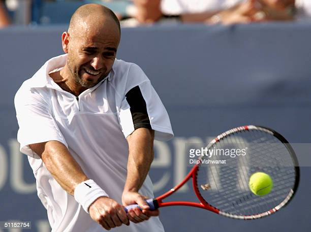 Andre Agassi of the United States returns a ball to Lleyton Hewitt of Australia during the Western and Southern Financial Group Masters tournament on...