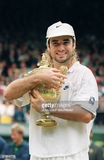 Andre Agassi of the United States smiles as he holds his trophee after beating Croatia's Goran Ivanisevic in five sets in the men's singles final at...