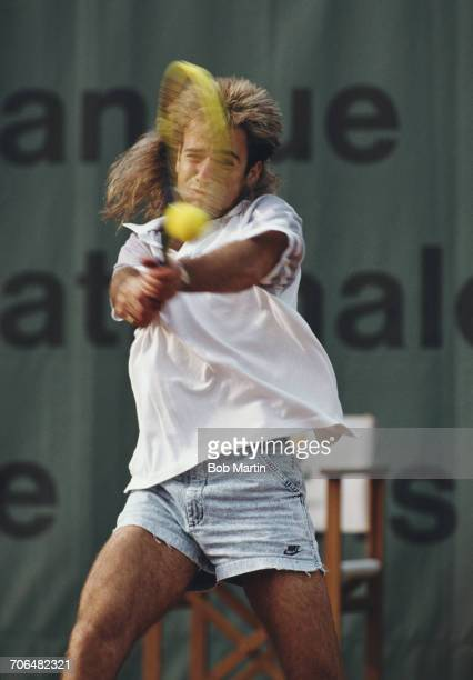 Andre Agassi of the United States wearing his jean style shorts makes a double hand return during a Men's Singles match during the French Open Tennis...