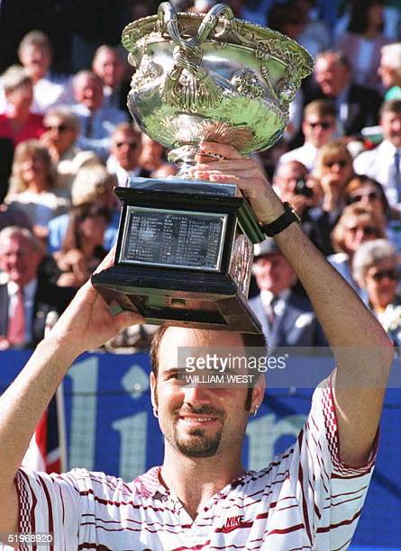Andre Agassi of the US holds up the champion's trophy after winning the Australian Open men's singles title 29 January 1995 Agassi beat top seed and...
