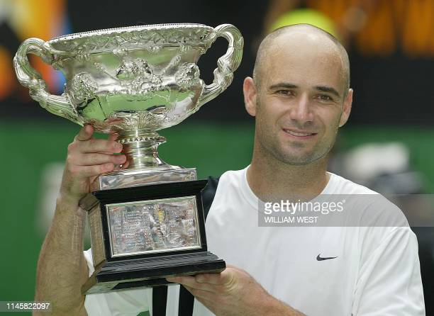 Andre Agassi of the US poses with the winner's trophy following his victory over Rainer Schuettler of Germany in the men's singles final at the...