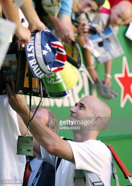 Andre Agassi of the US signs autographs for fans following his victory due to forfeit over Guillermo Coria of Argentina in their fourth round men's...