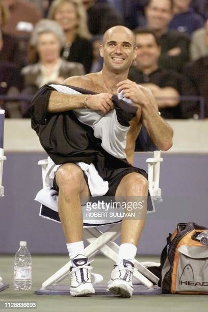 Andre Agassi of the US smiles while women cheer as he changes his shirt between games against Nicklas Kulti of Sweeden 30 August during their opening...