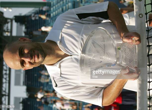 Andre Agassi of the USA poses at the net with his trophy after he defeated Lleyton Hewitt of Australia in the championship match during the Western...