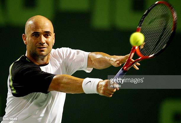 Andre Agassi returns to Roger Federer of Switzerland during their semi-final match at the NASDAQ-100 Open at the Crandon Park Tennis Center on April...