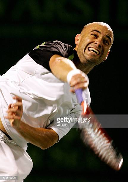 Andre Agassi serves to Roger Federer of Switzerland during their semi-final match at the NASDAQ-100 Open at the Crandon Park Tennis Center on April...