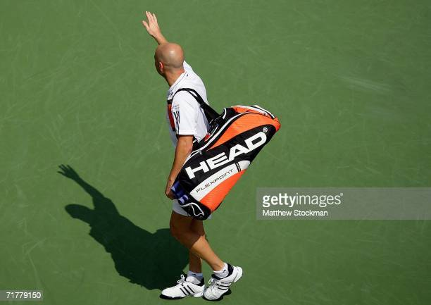 Andre Agassi waves to the crowd as he leaves the court for the final time after being defeated by Benjamin Becker of Germany in four sets during the...