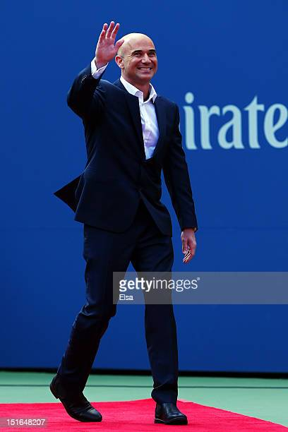 Andre Agassi waves to the crowd as he walks out for a ceremony honouring his career prior to the women's singles final match between Serena Williams...
