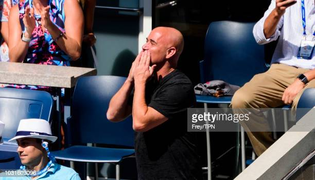 Andre Agassi waves to the crowd while watching Marin Cilic of Croatia in action against Kei Nishikori of Japan in the quarter finals of the US Open...