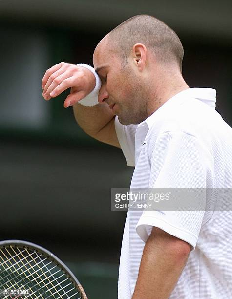 Andre Agassi wipes his forehead after loosing a point during his semifinal match at the Wimbledon championships against Australian Patrick Rafter on...