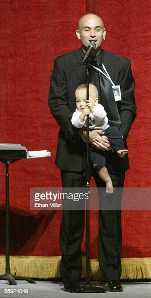 Andre Agassi's 11monthold son Jaden Agassi grabs the microphone stand as his father speaks at an auction during Andre Agassi's Grand Slam for...