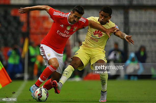 Andre Almeida of Benfica struggles for the ball with Michael Arroyo of America during a match between America and Benfica as part of the...