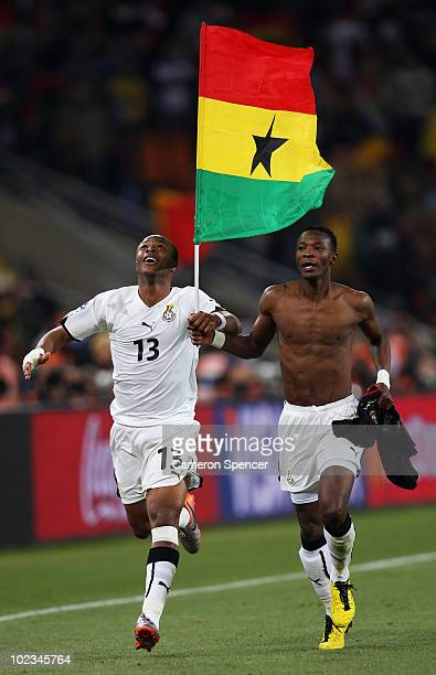 Andre Ayew and John Pantsil of Ghana celebrate with a national flag having qualified for the next round, despite losing the match, during the 2010...