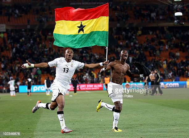 Andre Ayew and John Pantsil of Ghana celebrate with a national flag having qualified for the next round despite losing the match during the 2010 FIFA...