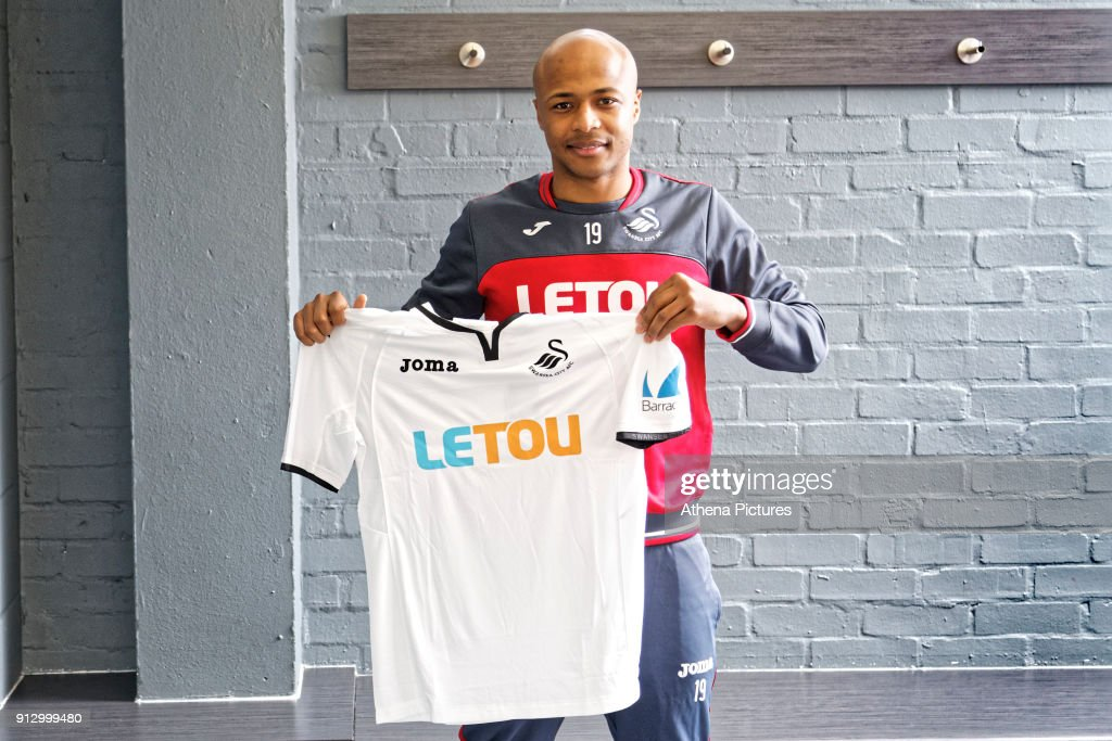 Andre Ayew holds a team shirt as he is unveiled as a new Swansea City signing at The Fairwood Training Ground on February 01, 2018 in Swansea, Wales.
