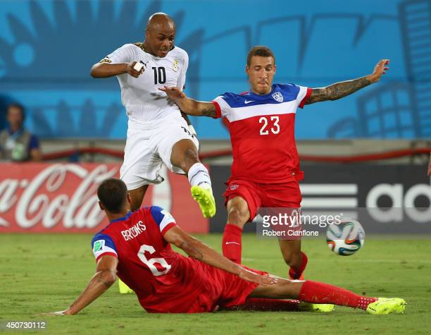 Andre Ayew of Ghana shoots and scores his team's first goal past John Brooks and Fabian Johnson of the United States during the 2014 FIFA World Cup...
