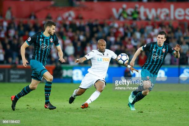 Andre Ayew of Swansea City breaks through the middle of Jeremy Pied and PierreEmile Hojbjerg of Southampton during the Premier League match between...