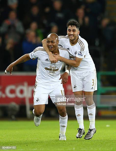 Andre Ayew of Swansea City celebrates scoring his team's second goal with his team mate Neil Taylor during the Barclays Premier League match between...