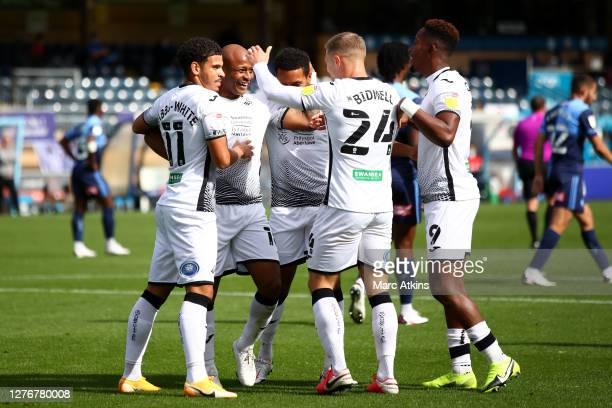 Andre Ayew of Swansea City celebrates with teammates after scoring his team's first goal during the Sky Bet Championship match between Wycombe...