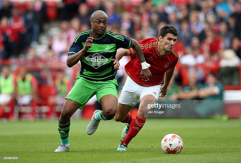Andre Ayew of Swansea City controls the ball from Jack Hobbs of Nottingham Forest during the pre season friendly match between Nottingham Forest and Swansea City at City Ground on July 25, 2015 in Nottingham, England.