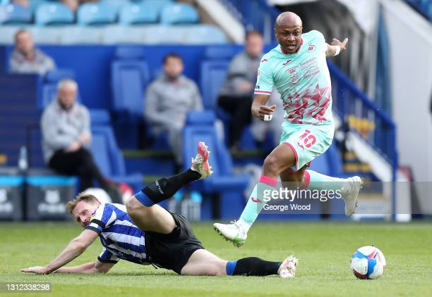Andre Ayew of Swansea City evades a tackle by Tom Lees of Sheffield Wednesday during the Sky Bet Championship match between Sheffield Wednesday and...