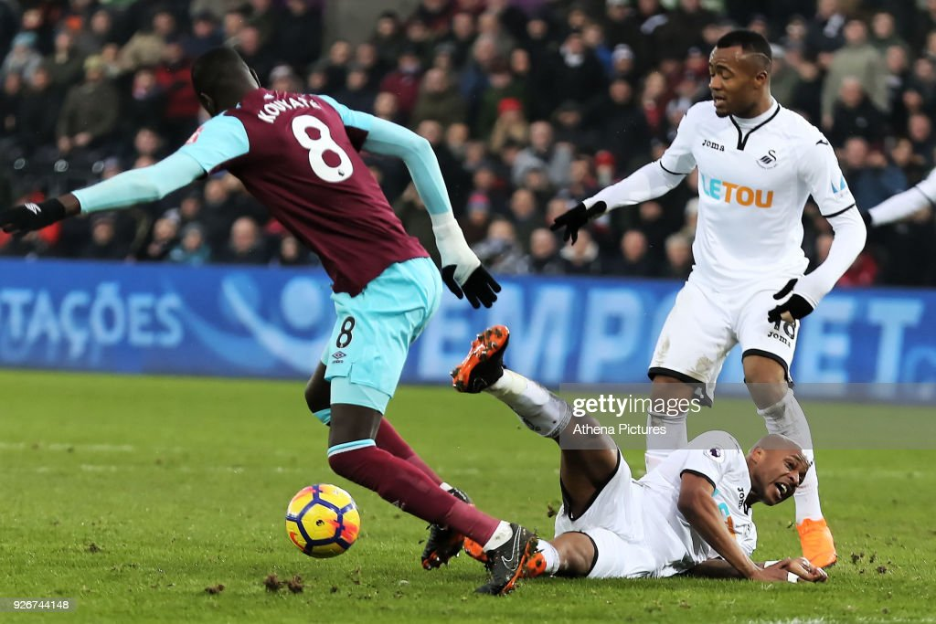 Andre Ayew of Swansea City (C) is brought down by Cheikhou Kouyate of West Ham (L) for which referee Martin Atkinson gave a penalty during the Premier League match between Swansea City and West Ham United at The Liberty Stadium on March 3, 2018 in Swansea, Wales.