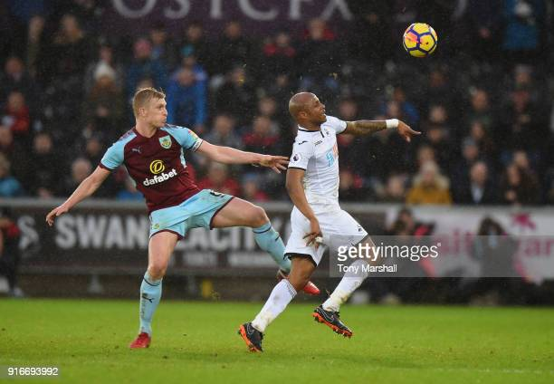 Andre Ayew of Swansea City is tackled by Ben Mee of Burnley during the Premier League match between Swansea City and Burnley at Liberty Stadium on...